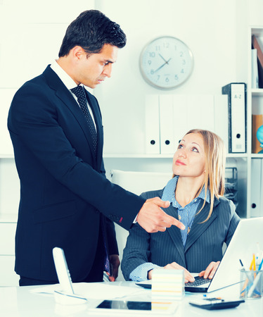 Dissatisfied manager scolding frustrated female assistant in office Foto de archivo