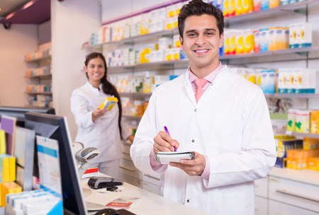 Professional american pharmaceutists at reception of drugstore ready to help