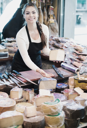 Cheerful young shopgirl selling cheese in a delicatessen store