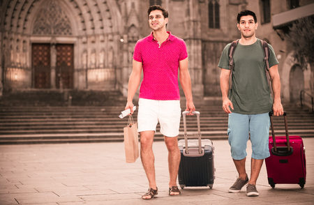 Happy cheerful positive men tourists are walking with suitcases in unknown city.