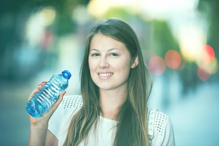 Attractive girl drinking water during walk around city in hot summer day