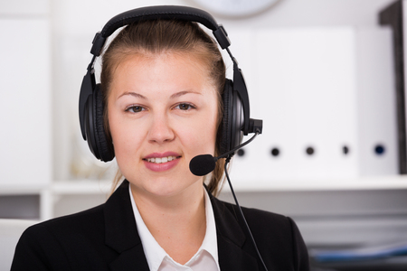 Portrait of young dispatcher in black suit which is talking by headset with client in the office.