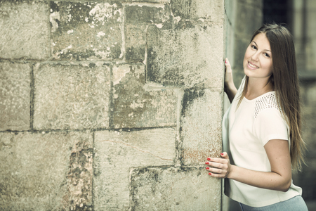 Romantic girl peeking out from behind cathedral wall looking at camera, copyspace