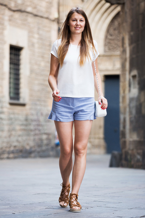 Attractive young woman in casuals walking along ancient street