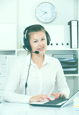 Young female trainee is working at a computer and talking by headset with client in the office.