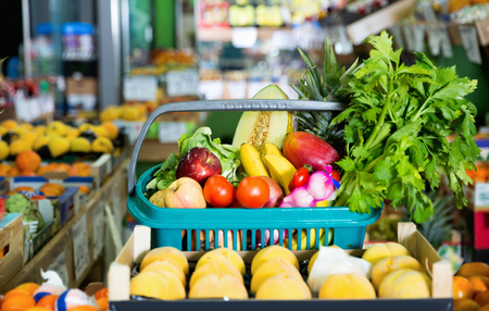 Shopping basket filled with fresh various delicious fruits and vegetables in store shelves Stock Photo