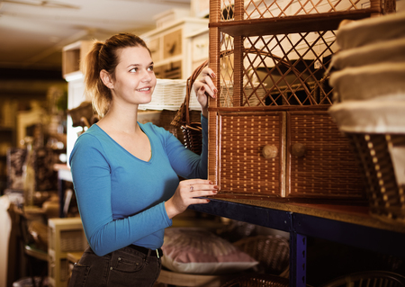 Young woman consumer near wicker commode in decor items store Stock Photo