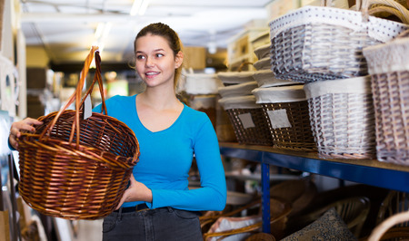 Happy female standing with wicker basket in decoration and furniture store