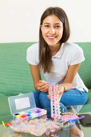 Lächelnde Frau macht Braslets mit elastischen Regenbogenwebstuhlbändern Standard-Bild - 93324806
