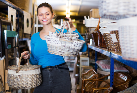cheeful beauty young girl customer standing with wicker basket in shop for decor