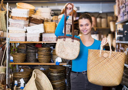 Young girl customer shows wicker bags in shop for decor