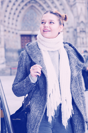 Cheerful young girl in scarf at the street in autumn season