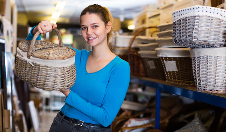 Ordinary female with picnic wicker basket in furniture store