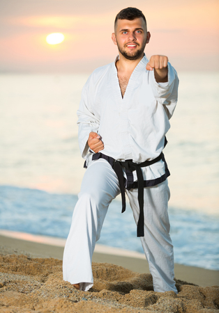 Young sportsman is practicing karate moves on the beach near the sea.