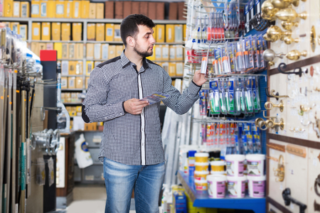 Smiling male client choosing new hot glue in houseware store  Imagens