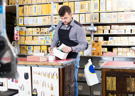 Young seller checking boxes with door details in houseware store