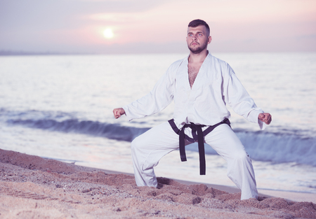 Concentrated active guy doing karate poses at  sunset sea shore