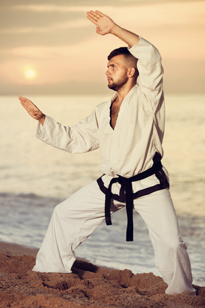 Diligent friendly smiling  pleasant guy doing karate poses at  sunset sea shore