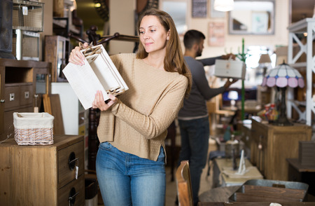 Young woman looking for stylish knickknacks for apartment in shop of secondhand furniture