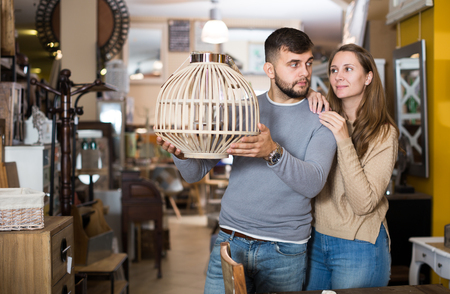 Loving couple looking for stylish hanging lamp in shop of secondhand furniture Banque d'images
