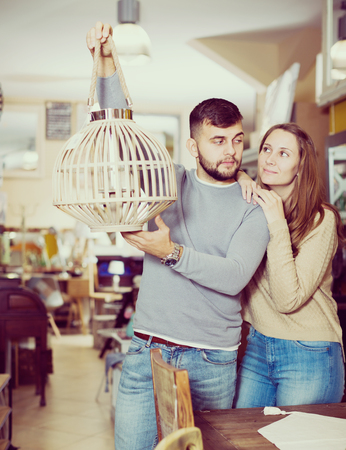 Happy couple with vintage suspended lamp in apartment crowded of old furniture Stock Photo