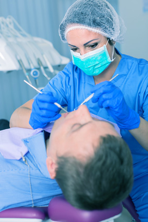 dentist professional filling teeth for man patient sitting in medical chair