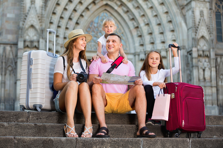 Happy positive smiling family of tourists resting on stairs reading paper map