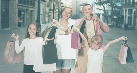 Positive family with children smiling and holding shopping bags in the town Stock Photo