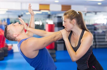 Young woman and her trainer are practicing captures on the self-defense course in gym