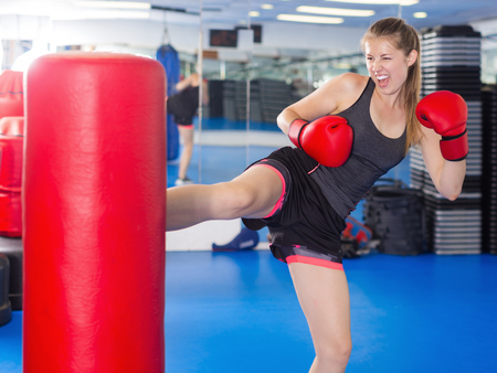 Portrait of active woman practicing with punching bag in box gym
