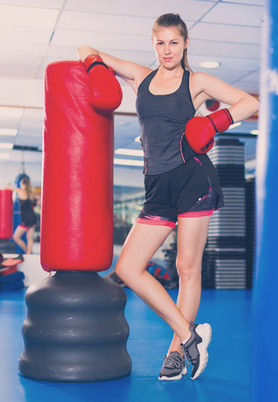 Potrait of smiling cheerful  woman boxer who is standing near punching bag in time training in gym.