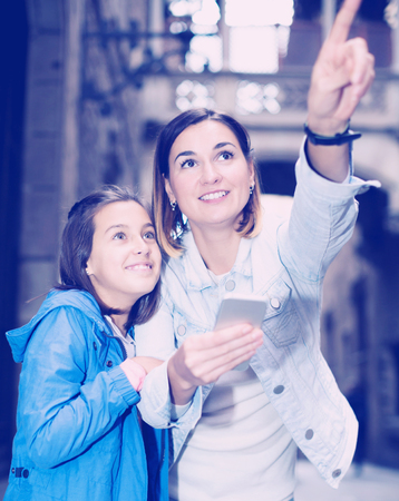 Attractive mother and daughter consulting guide in phone during sightseeing tour