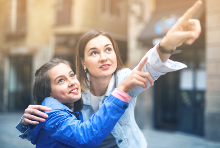Young happy mother and daughter paying attention to sight during sightseeing tour Stock Photo