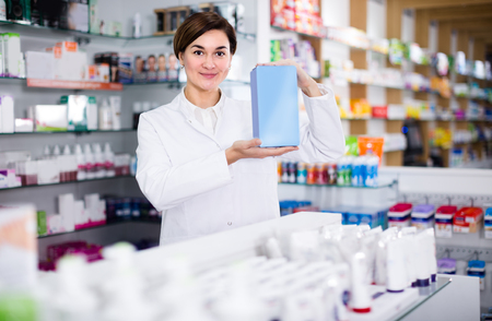 Professional female pharmacist is showing right drug in pharmacy.  Stock Photo