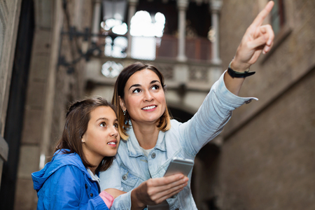 Young happy cheerful mother and daughter looking at guide in phone during sightseeing tour