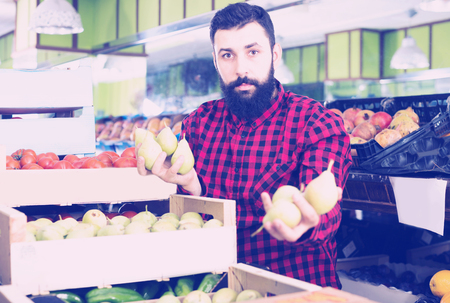 Shop assistant demonstrating pears in grocery shop
