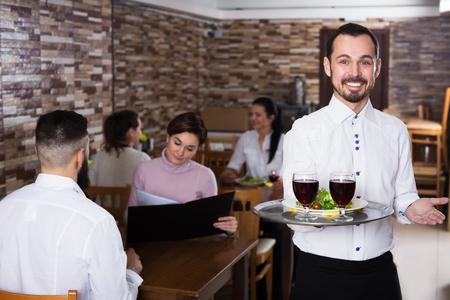 Positive man waiter demonstrating rustic restaurant to visitors