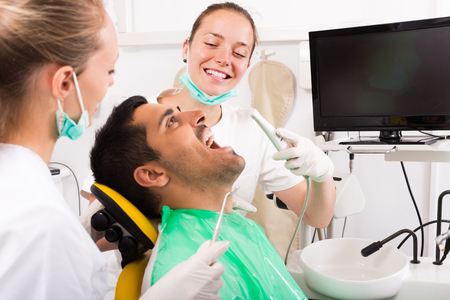 Young man and positive dental clinic crew during teeth check up. Selective focus