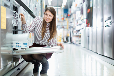 Modern  positive female housewife buying dishwasher in domestic appliances section