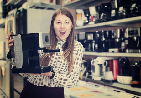 Portrait of delighted young woman with purchase in household appliances shop Stockfoto