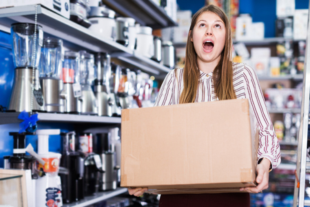 Positive girl holding cardboard box with purchase in section of house appliances