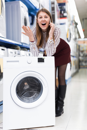Modern female having  mobile conversation in  shop of house appliances