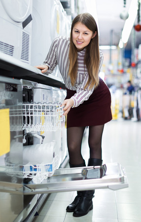Positive girl looking for functional dish washer in section of consumer electronics Stock Photo