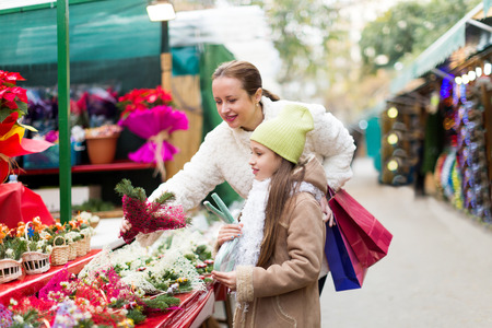 Woman with daughter buying Christmas floral composition with mistletoe  in market. Focus on girl Stock Photo