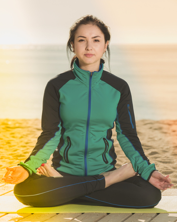 Young woman doing yoga poses cross-legged on beach in morning Stock Photo