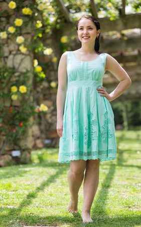 portrait of young positive germany woman in  dress  near roses in a garden Stock Photo