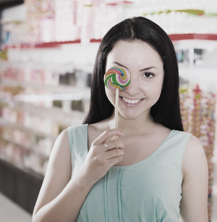 Pretty girl sucking   lollipop in the sweets store