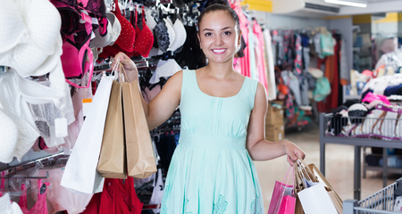 Smiling woman customer with shopping bags in lingerie shop