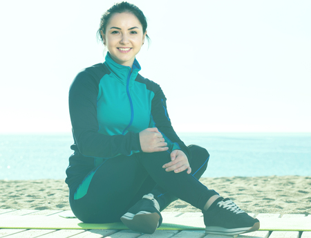 Young spanish woman ready to start morning training on beach