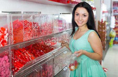 Young woman posing to photographer picking different candies with  scoop in  cellophane bag